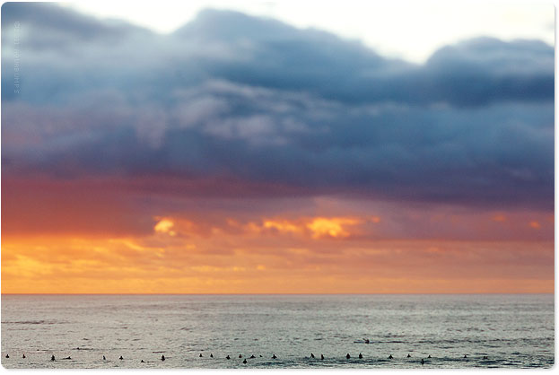 Surfers mesmerized by coloured skies
